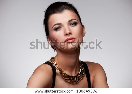 Portrait of luxury woman in exclusive jewelry and  black dress on natural background
