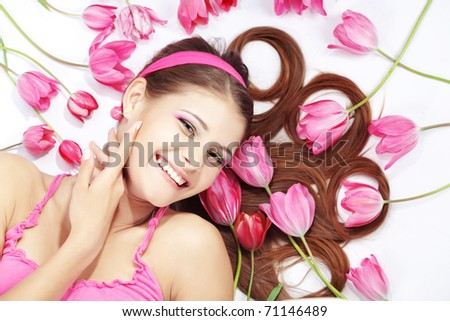 Portrait of lying beautiful wellbeing girl with spring tulips
