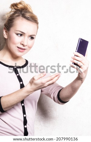Portrait of mad businesswoman texting on the mobile phone. Angry woman confused girl reading sms on smartphone. Misunderstanding. Indoor.