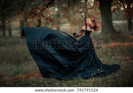 Stock Photo Portrait of magnificent Fashion gothic girl sitting near tree .Fantasy art work.Amazing red haired model in black dress and hat looking at camera and posing.Fairytale about young princess