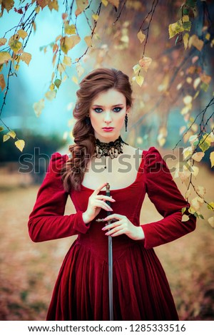 Stock Photo Portrait of magnificent Fashion gothic girl standing in autumn forest .Fantasy art work.Amazing red haired model in claret dress with a sword .Fairytale about young princess-warrior.
