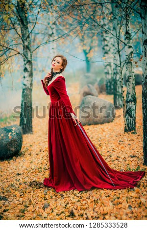 Portrait of magnificent Fashion gothic girl standing in autumn forest .Fantasy art work.Amazing red haired model in claret dress with a sword .Fairytale about young princess-warrior.  #1285333528