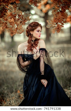 Stock Photo Portrait of magnificent Fashion gothic girl standing in forest .Fantasy art work.Amazing red haired model in black dress looking afar and posing.Fairytale about young princess