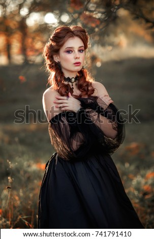 Stock Photo Portrait of magnificent Fashion gothic girl standing in glowing light .Fantasy art work.Amazing red haired model in black dress and hat looking at camera and posing.Fairytale about young princess