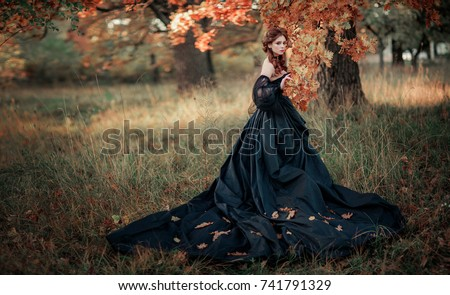 Portrait of magnificent Fashion gothic girl standing near tree .Fantasy art work.Amazing red haired model in black dress and hat looking at camera and posing.Fairytale about young princess