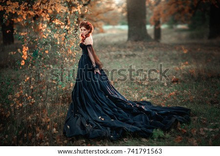 Stock Photo Portrait of magnificent Fashion gothic girl standing near tree .Fantasy art work.Amazing red haired model in black dress and hat looking at camera and posing.Fairytale about young princess