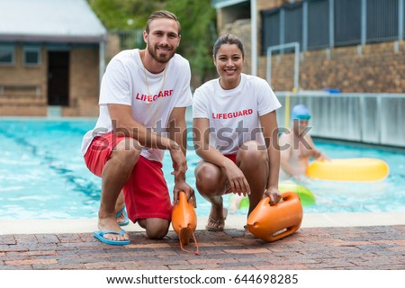 Portrait of male and female lifeguards holding rescue cans at poolside Foto stock ©