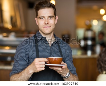 Portrait of male barista standing in cafe with cup of coffee