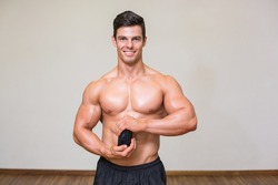 Portrait of male body builder holding bottle with supplements in gym