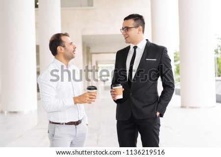 Portrait of male business colleagues drinking coffee and talking. Two mid adult businessmen communicating in office corridor. Coffee break concept #1136219516