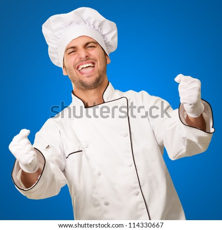 Portrait Of Male Chef Cheering On Blue Background