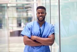 Portrait Of Male Doctor Wearing Scrubs Standing In Modern Hospital Building