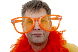 Portrait of male Dutch soccer fan with big orange glasses over white background