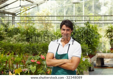 portrait of male florist looking at camera with arms folded - stock photo
