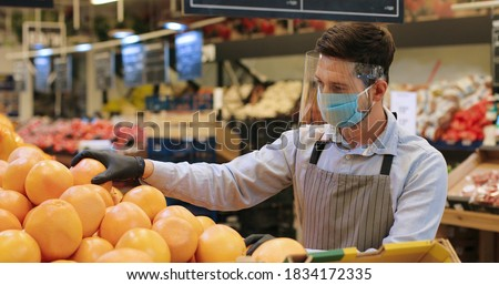 Portrait of male food store employee in face protection shield and apron standing in store and sorting fruits. Handsome Caucasian man seller in mask working indoor. Supermarket concept Stock foto ©
