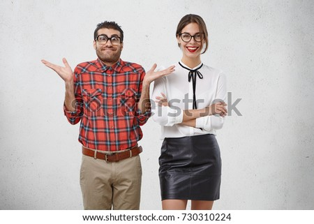Portrait of male geek has puzzled expression, looks doubtfully, feels indecisive about his future plans. Cheerful woman with red lips, wears white blouse and black skirt, demonstrates charming smile