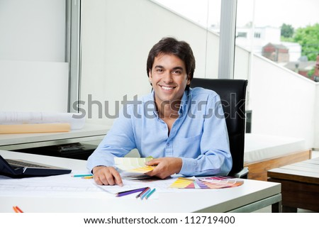 Portrait of male interior designer working at office with color swatches