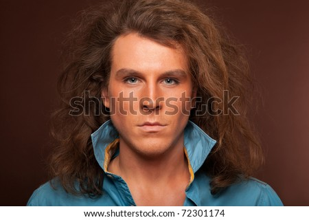 Portrait of male model with long hair and makeup on brown background
