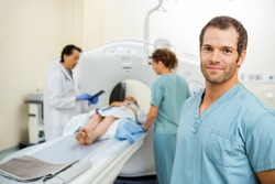 Portrait of male nurse with colleague and radiologist preparing patient for CT scan in examination room