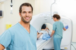 Portrait of male nurse with colleague preparing patient for CT scan in examination room