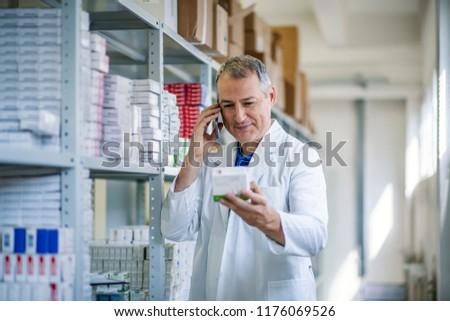 Portrait of male pharmacist chemist man in pharmacy drugstore. Medical factory supplies storage indoor with chemist man. Cheerful pharmacist chemist man working in pharmacy drugstore