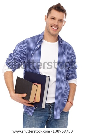 Portrait of male student standing with books in hands, smiling.