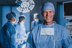 Portrait of male surgeon with team of doctors on background in operation room.