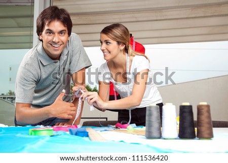 Portrait of male tailor with female assistant cutting ribbon - stock photo