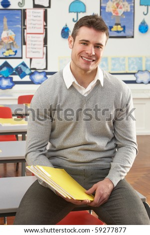 Portrait Of Male Teacher Sitting At Desk In Classroom