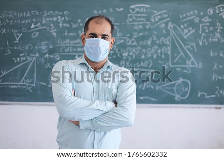 Portrait of male teacher wearing mask standing against blackboard teaching mathematics in classroom, school reopen after lockdown due to covid-19 pandemic. new strain of coronavirus, second wave.