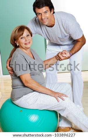 Portrait of male therapist helping senior woman sitting on fitness ball - stock photo