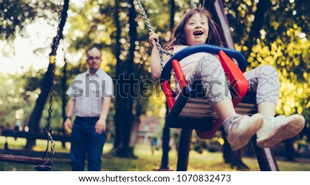 Portrait of man and girl with down syndrome swinging