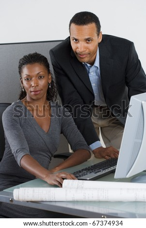 Portrait of man and woman at desk with computer