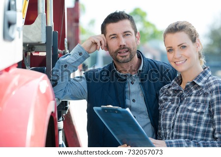 portrait of man and woman holding clipboard next to truck