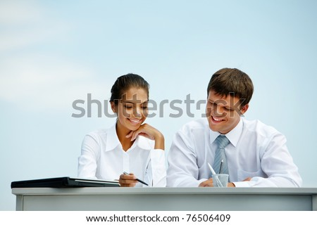 Portrait of man and woman sitting at the desk and interacting with each other
