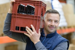 portrait of man carrying crate of beer