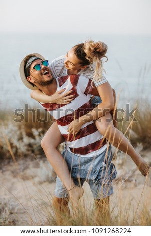 Portrait of man carrying girlfriend on his back along the sea shore. Man giving piggyback ride to girlfriend on the beach.