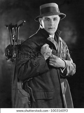 Portrait of man carrying golf clubs