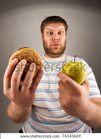 Portrait of man choosing between hamburger and green apple