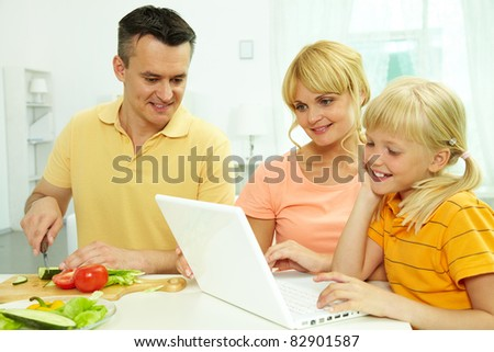 Portrait of man cutting vegetables for salad while his wife and daughter working with laptop the kitchen