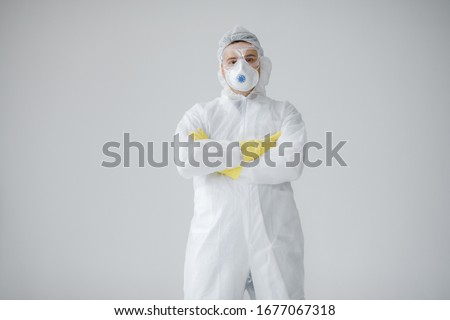 Portrait of man doctor in protective clothes during coronavirus pandemic. Epidemic, pandemic of coronavirus covid 19. Doctor, patient in respirator.