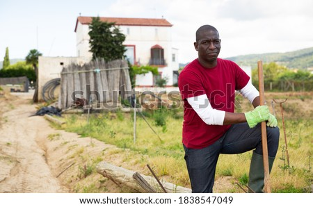 Portrait of man gardener with mattock during working at land outdoor Stock photo ©