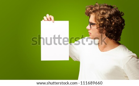 Portrait Of Man Holding A Blank Paper Isolated On Green Background - stock photo