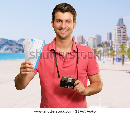 Portrait Of Man Holding Camera And Boarding Pass, Outdoor