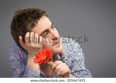 Portrait of man holding red flower , isolated on grey background