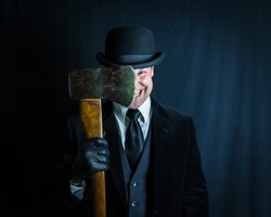 Portrait of Man in Dark Suit and Bowler Hat Holding Axe Blade Next to His Face. Concept of Horror Movie Murderer. Maniacal Grin and Violent Insanity.