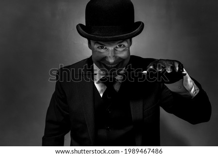 Portrait of Man in Dark Suit and Bowler Hat Holding Knife and Smiling Maniacally  Сток-фото ©
