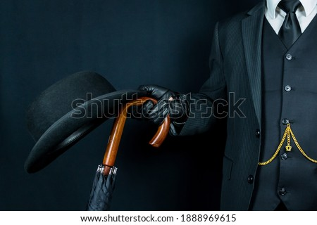 Portrait of Man in Dark Suit and Leather Gloves Holding Bowler Hat and Umbrella on Black Background. Classic and Eccentric British Gentleman. Retro Style and Vintage Fashion Stockfoto ©