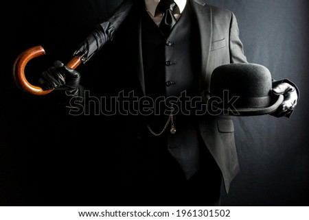Portrait of Man in Dark Suit and Leather Gloves Holding Umbrella and Bowler Hat on Black Background. Concept of Classic British Gentleman. Retro Style and Vintage Fashion. Stockfoto ©