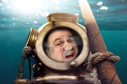 Portrait of man in old diving suit and helmet under water. Funny diver in retro equipment with face crushed on glass.